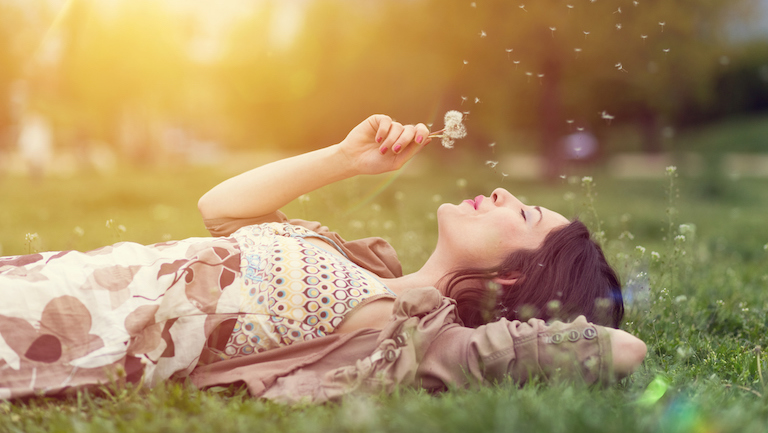 Young woman lying down in the grass and blowing dandelion